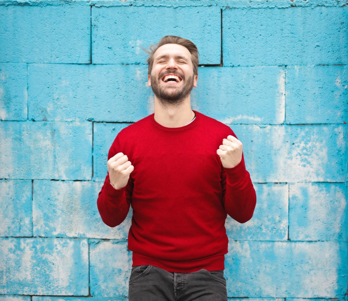 excited man in red sweater in front of blue wall